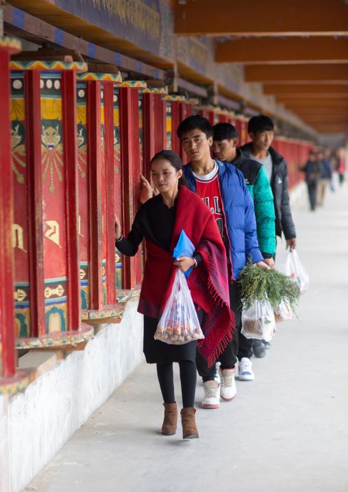 Tibetan pilgrims turning prayer wheels in a Rongwo monastery, Tongren County, Longwu, China