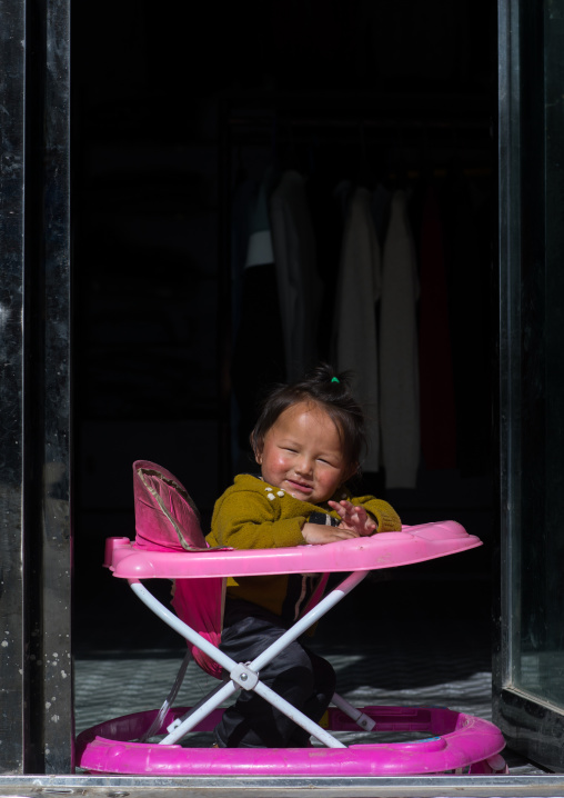 Portrait of a girl sit in her baby walker, Qinghai province, Tsekhog, China