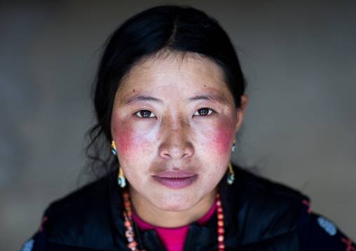 Portrait of a tibetan nomad woman with her cheeks reddened by the harsh weather, Qinghai province, Tsekhog, China