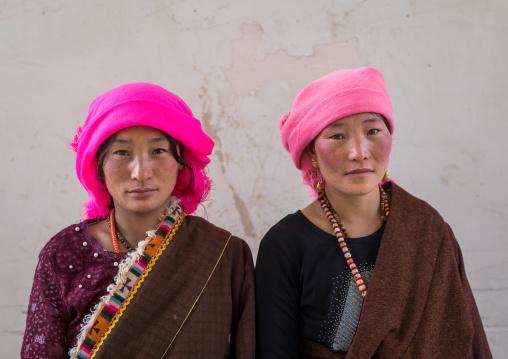 Portrait of tibetan nomads women with a pink headwears, Qinghai province, Tsekhog, China