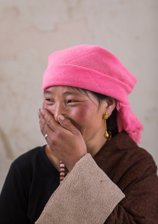 Portrait of a tibetan nomad woman with a pink headwear laughing, Qinghai province, Tsekhog, China