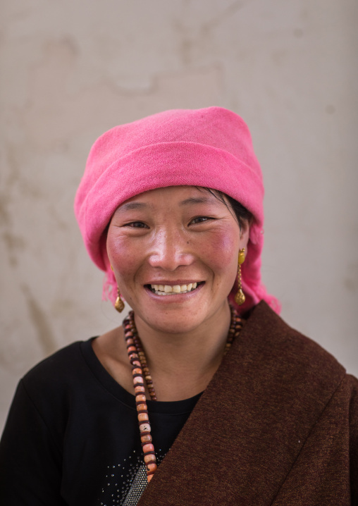 Portrait of a tibetan nomad woman with a pink headwear, Qinghai province, Tsekhog, China