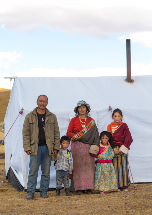 Portrait of a tibetan nomad family living in a tent in the grasslands, Qinghai province, Tsekhog, China