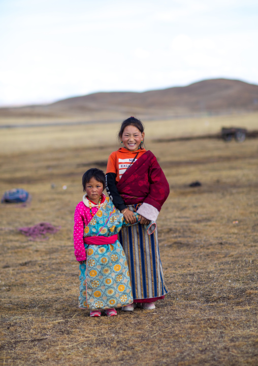 Portrait of a tibetan nomad children with their cheeks reddened by the harsh weather, Qinghai province, Tsekhog, China