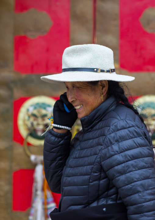 Tibetan woman calling on her mobile phone in Hezuo monastery, Gansu province, Hezuo, China