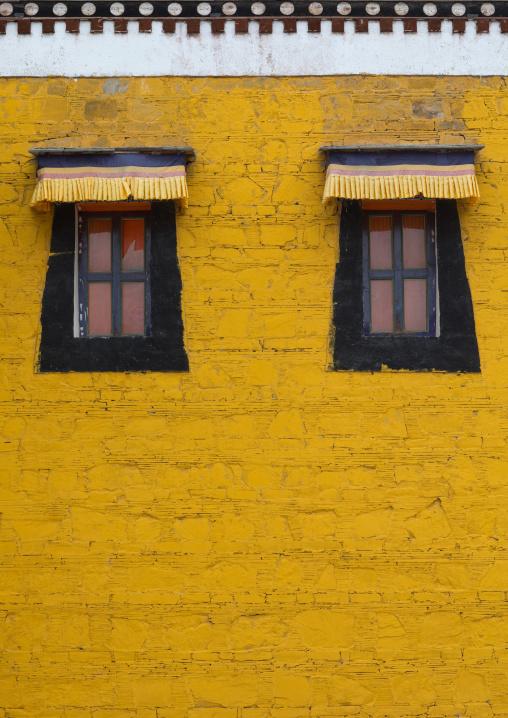 Typical tibetan windows on a yellow wall in Hezuo monastery, Gansu province, Hezuo, China
