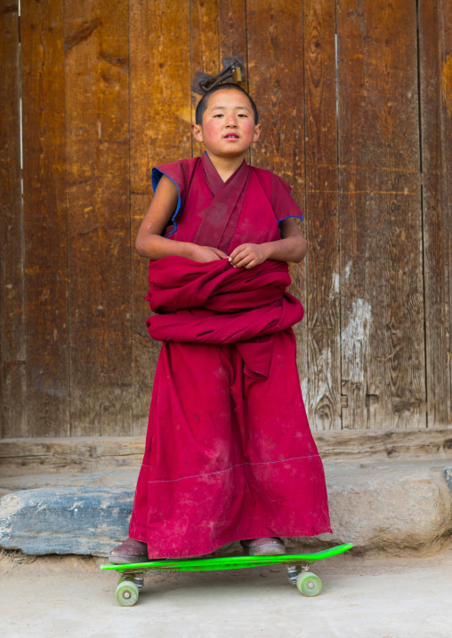 Young tibetan monk on a skateboard in Lhachub monastery, Gansu province, Lhachub, China