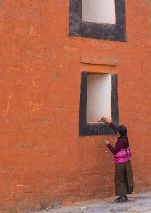 Tibetan pilgrim woman putting a donation on a temple window in Labrang monastery, Gansu province, Labrang, China
