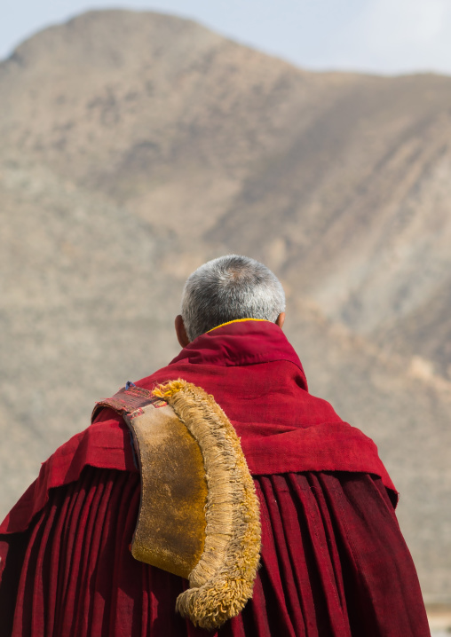Tibetan monk wearing robe and yellow hat of the gelug order in Labrang monastery, Gansu province, Labrang, China