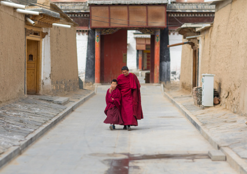 Tibetan monks coming out of a temple in Labrang monastery, Gansu province, Labrang, China