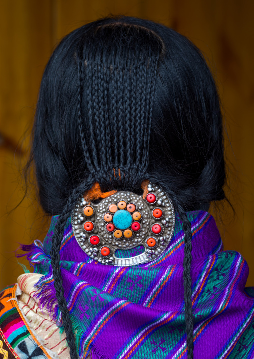 Nyingma tibetan nomad wearing a silver and coral plaque in her braided hair, Gansu province, Labrang, China