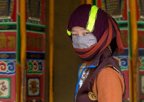 Tibetan pilgrim woman turning huge prayer wheels in Labrang monastery, Gansu province, Labrang, China