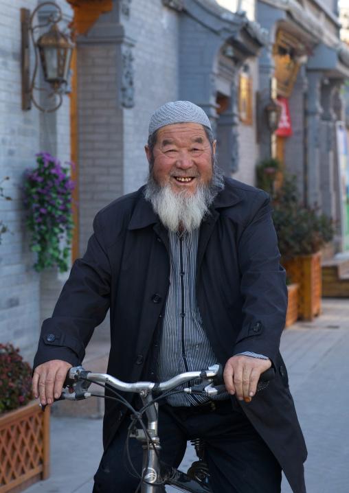 Smiling hui muslim man riding a bicycle in the street, Gansu province, Linxia, China