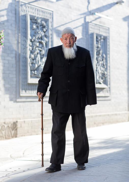 Hui muslim man walking with cane in the street, Gansu province, Linxia, China