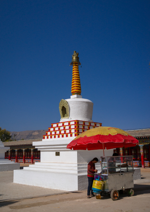 Woman selling food in front of a stupa in Wutun si monastery, Qinghai province, Wutun, China