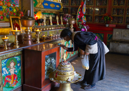 Tibetan woman praying inside a temple of Rongwo monastery, Tongren County, Longwu, China