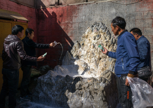 Tibetan men throwing milk in a temple of Rongwo monastery, Tongren County, Longwu, China