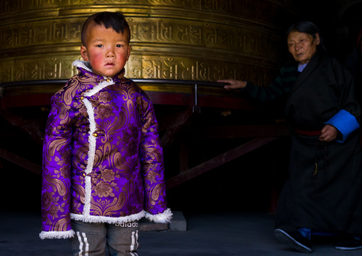 Portrait of a tibetan nomad boy with his cheeks reddened by the harsh weather in front of a prayer wheel in Rongwo monastery, Tongren County, Longwu, China