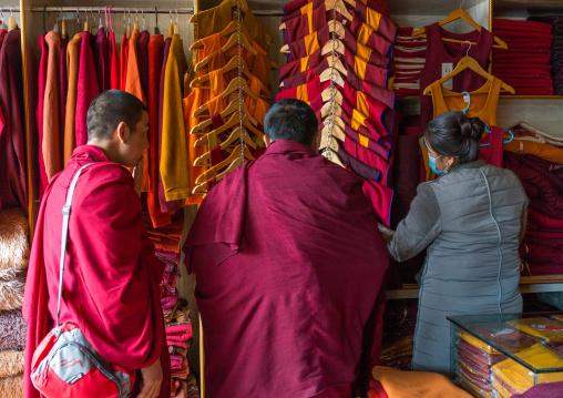 Monks buying robes in a shop, Tongren County, Longwu, China