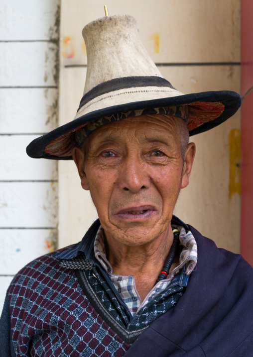 Portrait of an old tibetan man with a traditional and conical hat, Tongren County, Longwu, China