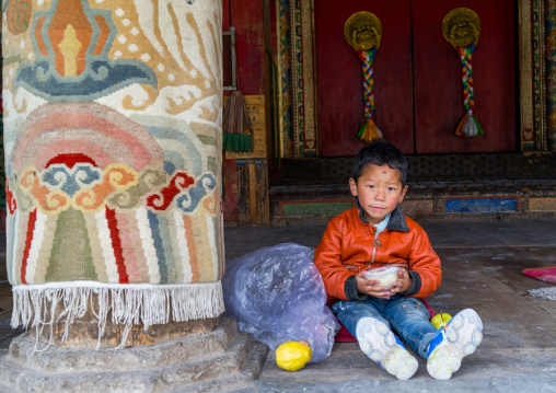 Tibetan boy eating in Rongwo monastery, Tongren County, Longwu, China