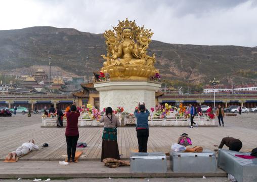Tibetan people praying in front of the  statue of the buddhist goddess tara outside longwu monastery, Tongren County, Longwu, China