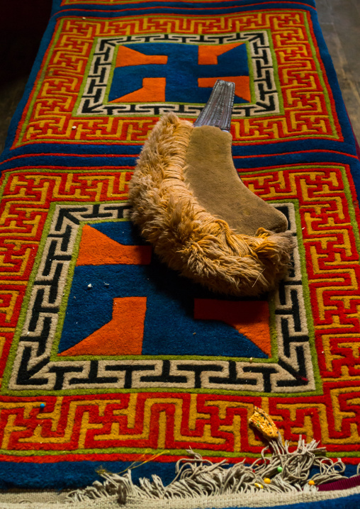 Yellow hat sect on a carpet with swastikas inside Bongya monastery, Qinghai province, Mosele, China