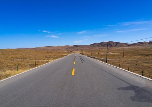 Empty road in rural landscape, Qinghai province, Tsekhog, China