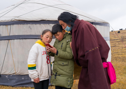 Portrait of a tibetan nomad family living in a yurt in the grasslands and looking at a mobile phone, Qinghai province, Sogzong, China