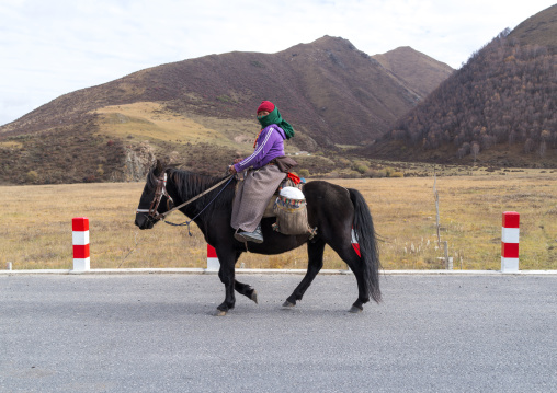 Tibetan woman on her horse, Qinghai province, Sogzong, China