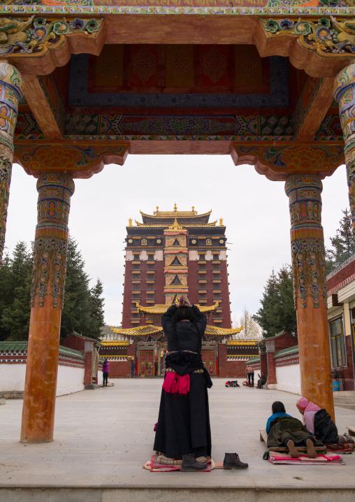 Tibetan pilgrims praying and prostrating in front of Hezuo monastery and its milarepa tower, Gansu province, Hezuo, China