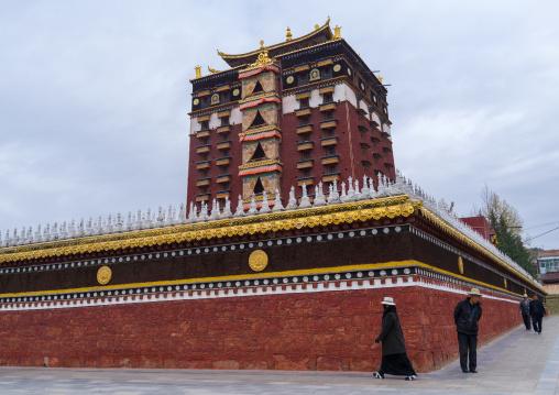 Tibetan pilgrim doing kora around Hezuo monastery and its milarepa tower, Gansu province, Hezuo, China