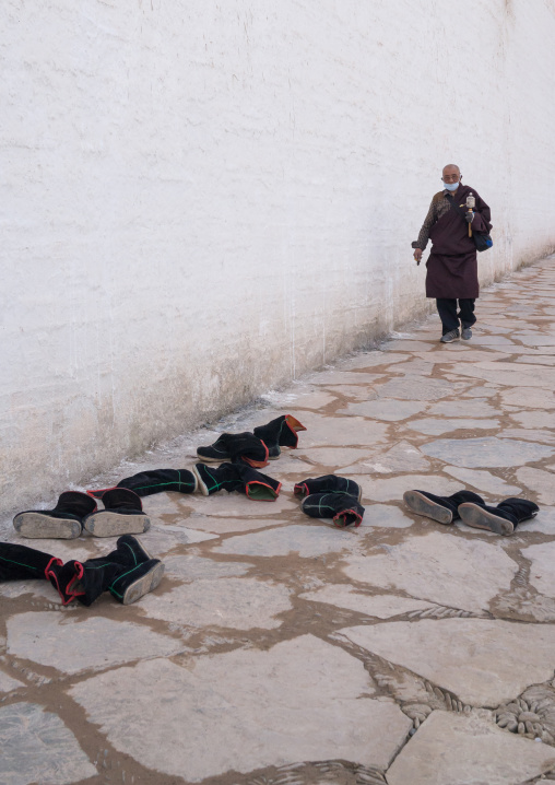 Tibetan monks boots in front of the entrance of a temple in Labrang monastery, Gansu province, Labrang, China