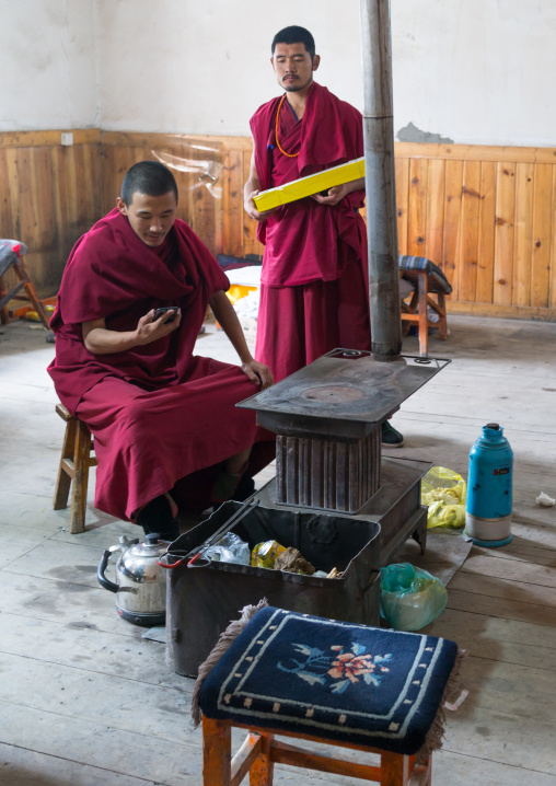 Tibetan monks in front of a stove, Gansu province, Labrang, China