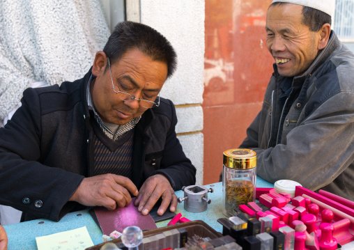 Carver making traditional chinese stamp in the street, Gansu province, Linxia, China