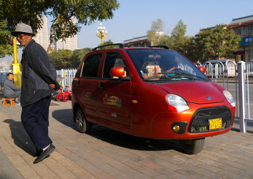 Cute small three-wheeled red chinese taxi in the street, Gansu province, Linxia, China