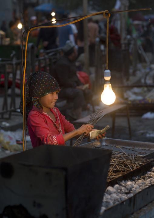 Young Uyghur Girl Preparing Skewers In The Night Market, Hotan, Xinjiang Uyghur Autonomous Region, China