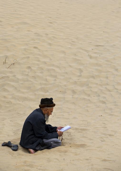 Uyghur Sufi Man Praying At Imam Asim Tomb In The Taklamakan Desert, Xinjiang Uyghur Autonomous Region, China