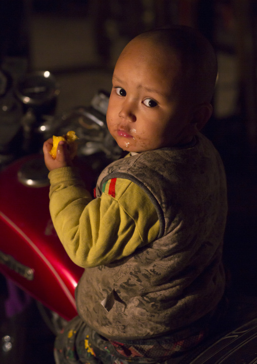 Uyghur Baby Eating A Fruit At Night Market, Hotan, Xinjiang Uyghur Autonomous Region, China