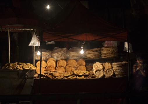 Young Uyghur Man Selling Bread In Night Market, Hotan, Xinjiang Uyghur Autonomous Region, China