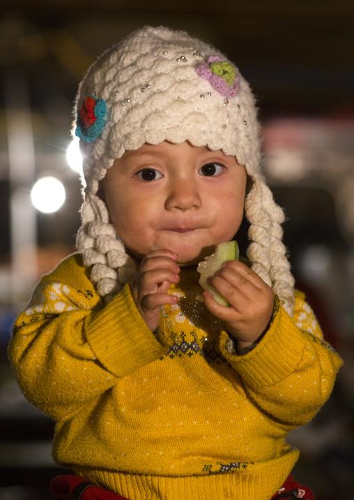 Uyghur Baby Eating A Piece Of Fruit, Night Market, Hotan, Xinjiang Uyghur Autonomous Region, China