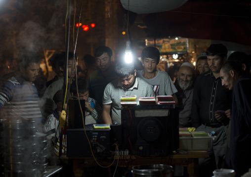 Man Selling Dvd In Night Market, Hotan, Xinjiang Uyghur Autonomous Region, China