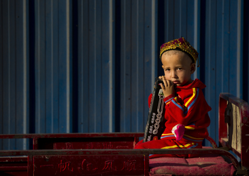 Uyghur Boy Waiting In A Cart, Yarkand, Xinjiang Uyghur Autonomous Region, China