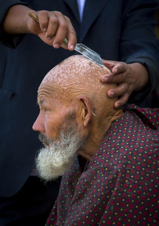 Uyghur Man Getting Shaved By A Barber At Serik Buya Market, Yarkand, Xinjiang Uyghur Autonomous Region, China