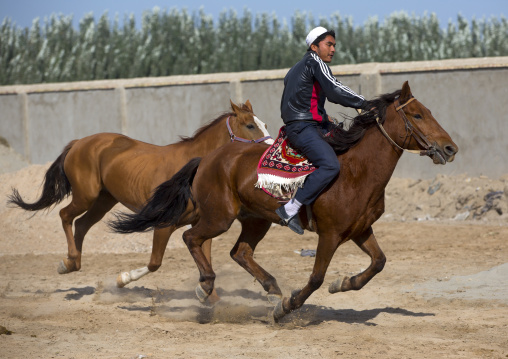 Young Uyghur Man Trying Out A Horse In Serik Buya Market, Yarkand, Xinjiang Uyghur Autonomous Region, China