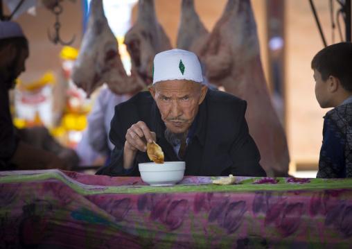 Old Uyghur Man Eating bread, Serik Buya Market, Yarkand, Xinjiang Uyghur Autonomous Region, China
