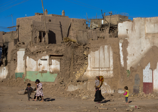 family passing in the Demolished Old Town Of Kashgar, Xinjiang Uyghur Autonomous Region, China