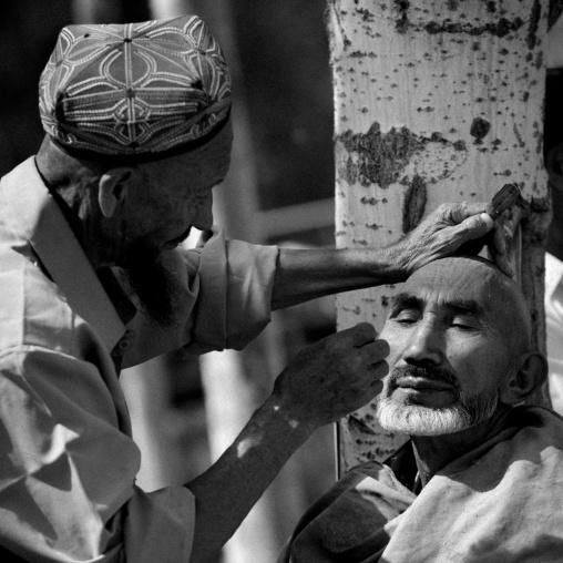 Uyghur Barber Shaving A Customer, Opal Village Market, Xinjiang, China, Xinjiang Uyghur Autonomous Region, China