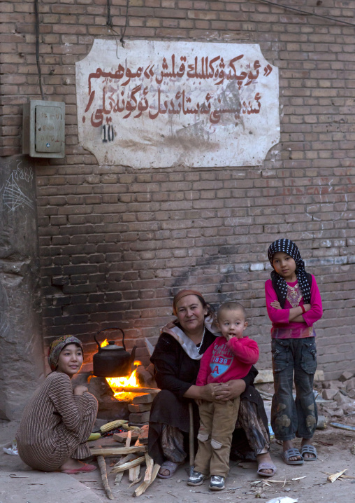 Uyghur Family making fire in the street, Kashgar, Xinjiang Uyghur Autonomous Region, China