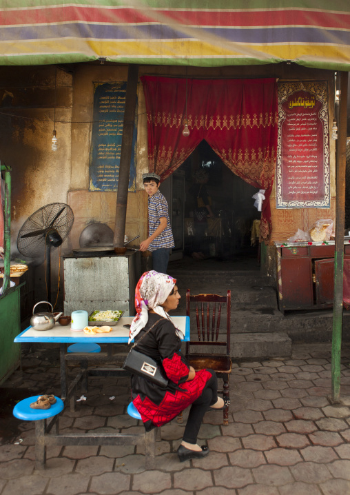 Young Uyghur Woman Waiting At The Table Of A Restaurant, And Cook, Keriya, Old Town, Xinjiang Uyghur Autonomous Region, China